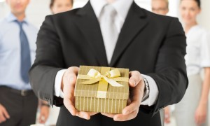 close up of man hands holding gift box in office