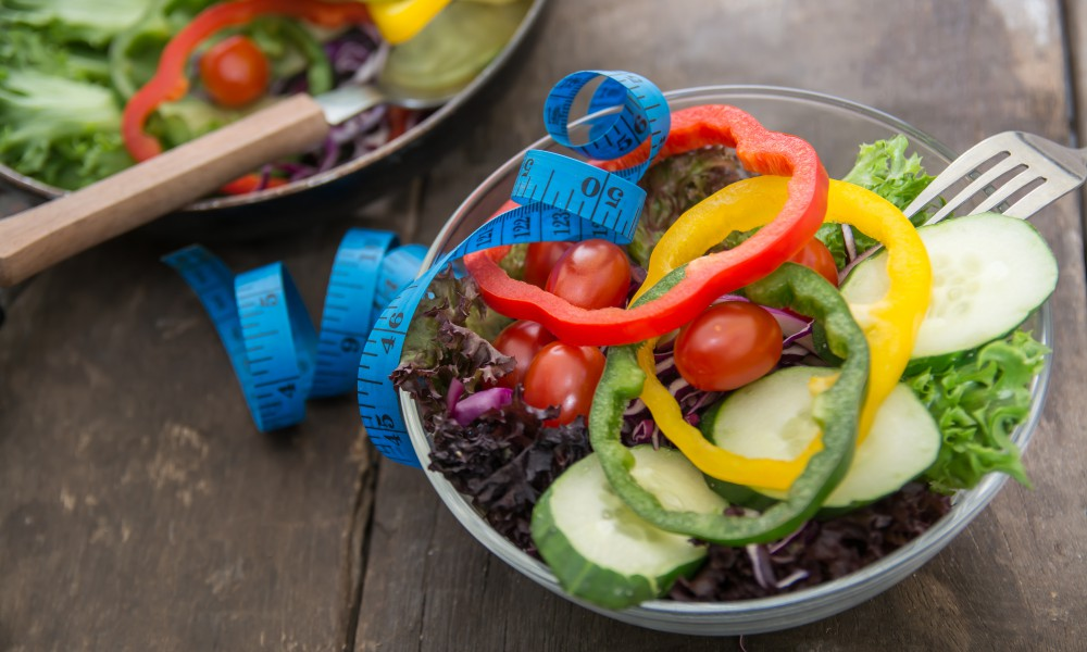 Fresh vegetables salad on  bowl with measuring tape over wooden background. Diet Food and healthy lifestyle concept.