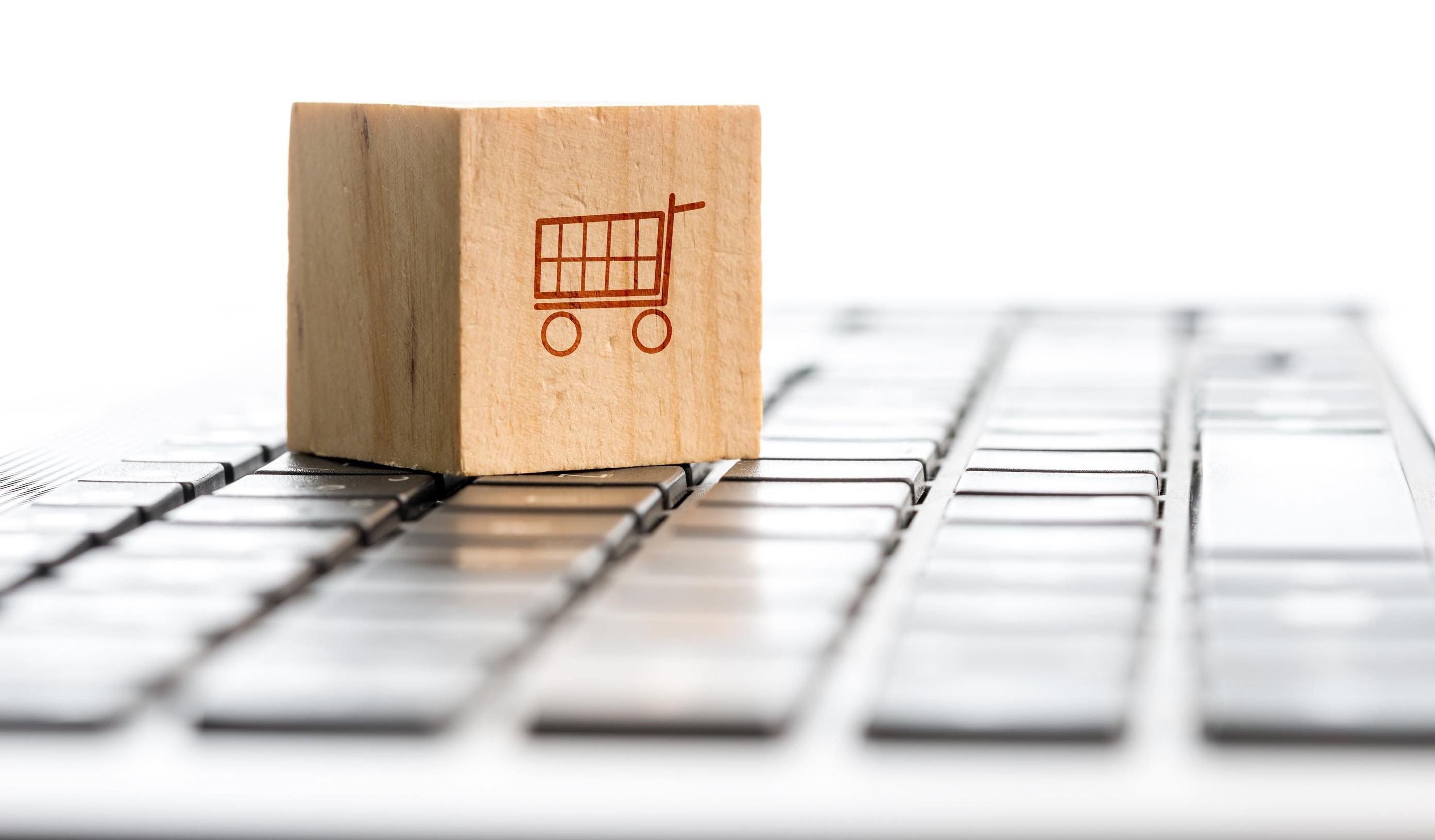 Online shopping and e-commerce concept with a wooden block with an icon of a shopping cart standing on a computer keyboard viewed low angle with copyspace.