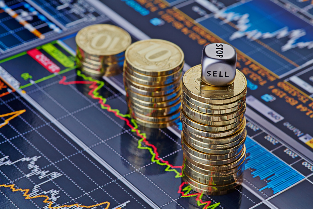 Downtrend stacks of golden coins and  the dices cube with the word SELL. Financial chart as background. Selective focus
